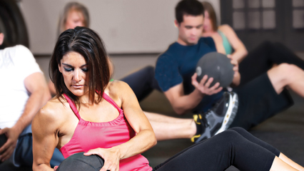 Group sitting and exercising with medicine balls